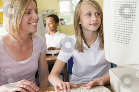 Teacher and schoolgirl studying in front of a school computer stock photo,  by Monkey Business Images
