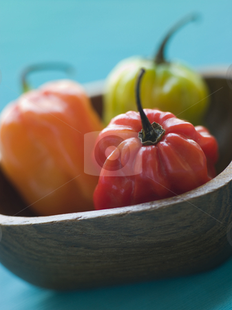 Scotch Bonnet Chilies In a Wooden Dish stock photo, Close up of Scotch Bonnet Chilies In a Wooden Dish by Monkey Business Images