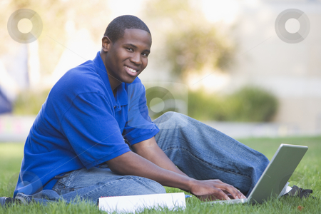 University student using laptop outside stock photo, Male university student using laptop outside by Monkey Business Images