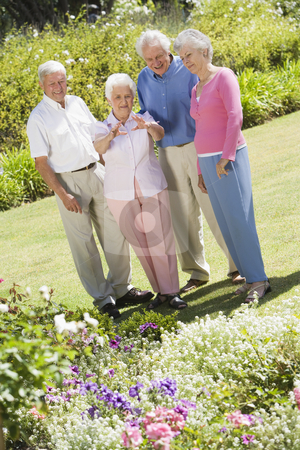 Group of senior friends in garden stock photo, Group of senior friends in garden admiring flowerbed by Monkey Business Images