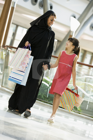 A Middle Eastern woman with a girl in a shopping mall stock photo,  by Monkey Business Images