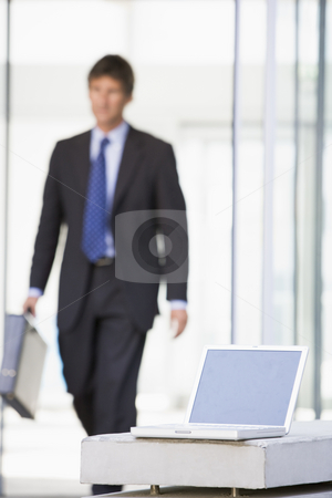 Laptop sitting in office lobby with businessman walking in stock photo,  by Monkey Business Images