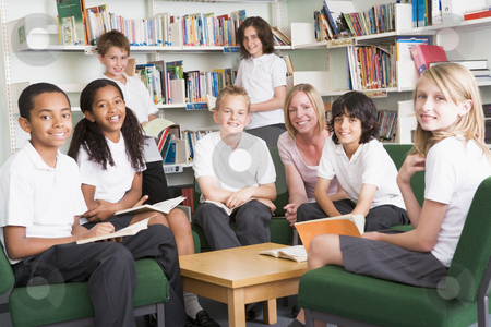 Junior school students working in a library stock photo,  by Monkey Business Images