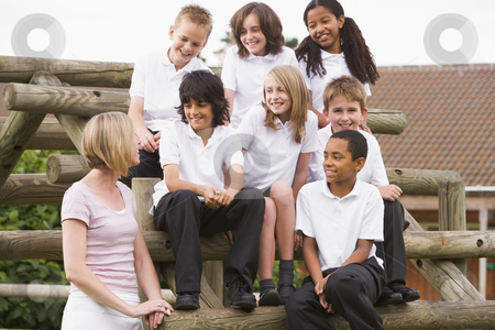 School children sitting on benches outside with their teacher stock photo,  by Monkey Business Images