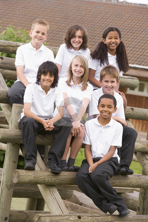 School children sitting on benches outside stock photo,  by Monkey Business Images