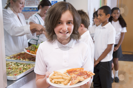 Schoolgirl holding plate of lunch in school cafeteria stock photo,  by Monkey Business Images