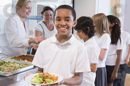 Schoolboy holding plate of lunch in school cafeteria stock photo,  by Monkey Business Images