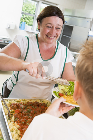 Lunchlady serving plate of lunch in school cafeteria stock photo,  by Monkey Business Images