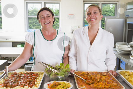 Lunchladies beside trays of food in school cafeteria stock photo,  by Monkey Business Images