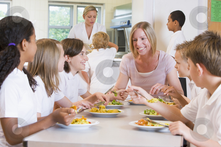 Teacher and schoolchildren enjoying their lunch in a school cafe stock photo,  by Monkey Business Images