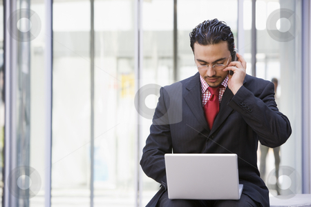 Businessman using laptop and mobile outside stock photo, Businessman using laptop and mobile outside office by Monkey Business Images