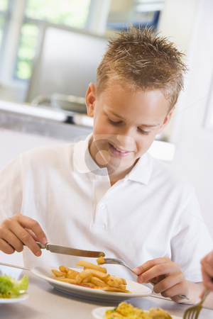 Schoolboy enjoying his lunch in a school cafeteria stock photo,  by Monkey Business Images