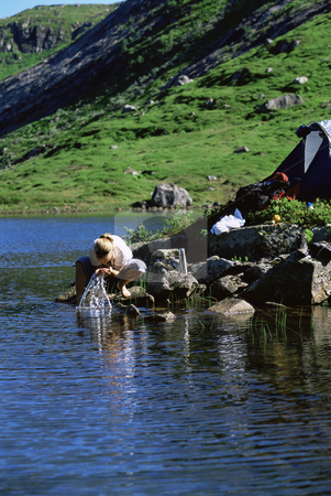 Young woman washing clothes in lake next to tent stock photo,  by Monkey Business Images