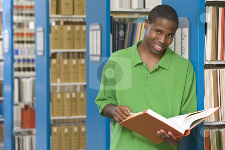 University student working in library stock photo, University student studying book in library by Monkey Business Images