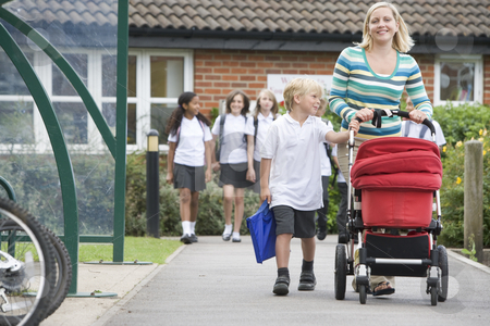 A woman with a pushchair walking her son home from school stock photo,  by Monkey Business Images