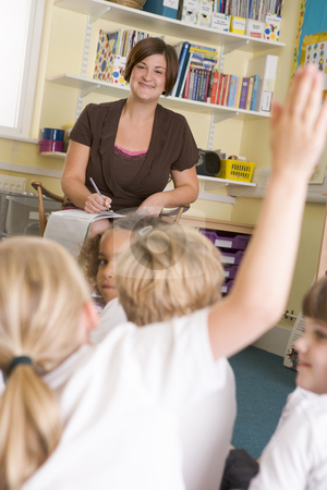 A teacher sits with schoolchildren in a primary class stock photo,  by Monkey Business Images