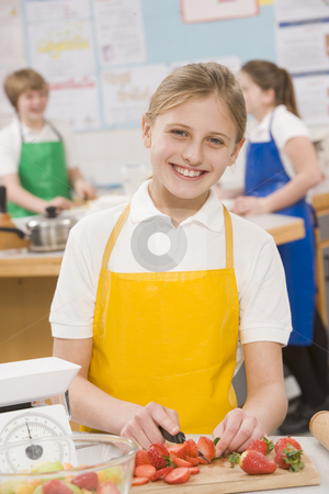 Schoolgirl at school in a cooking class stock photo,  by Monkey Business Images