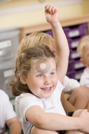 A schoolgirl raises her hand in a primary class stock photo,  by Monkey Business Images
