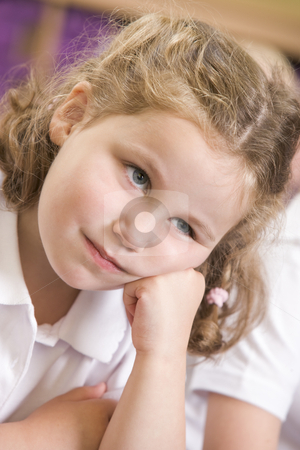 Bored schoolgirl sitting in primary class stock photo,  by Monkey Business Images