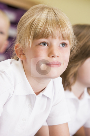 Schoolgirl sitting in primary class stock photo,  by Monkey Business Images