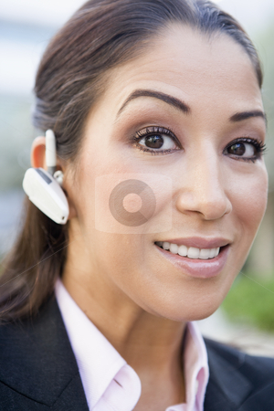 Businesswoman using bluetooth earpiece stock photo, Businesswoman using bluetooth earpiece outside by Monkey Business Images