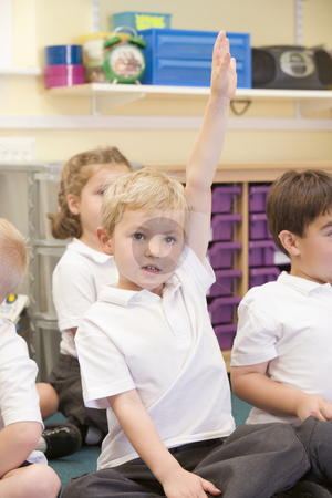 A schoolboy raises his hand in a primary class stock photo,  by Monkey Business Images