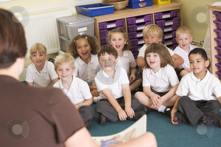 A teacher reads to schoolchildren in a primary class stock photo,  by Monkey Business Images