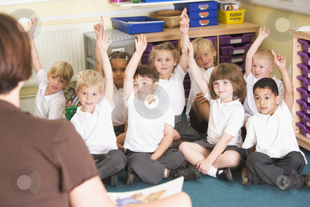 Schoolchildren raise their hand in a primary class stock photo,  by Monkey Business Images
