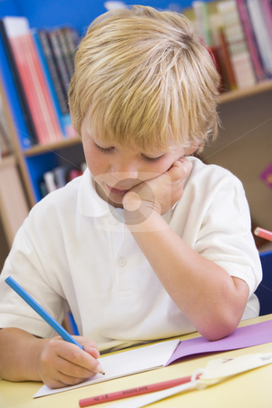 A schoolboy sitting in a primary class stock photo,  by Monkey Business Images