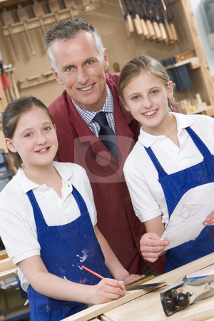 Schoolgirls and teacher in woodwork class stock photo,  by Monkey Business Images