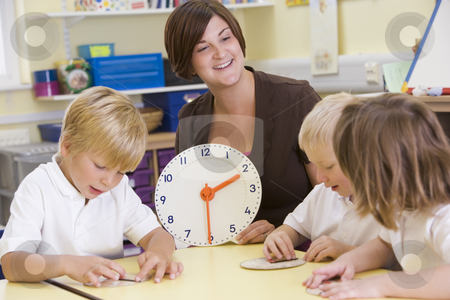 Teacher helping schoolchildren learn to tell time in primary cla stock photo,  by Monkey Business Images