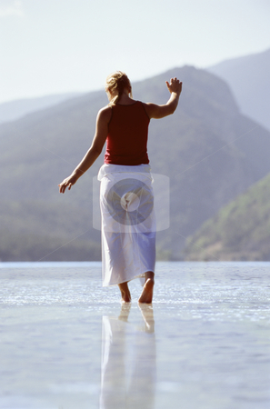 Young woman wading in lake stock photo,  by Monkey Business Images