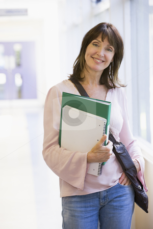 A woman with a backpack standing in a campus corridor stock photo,  by Monkey Business Images