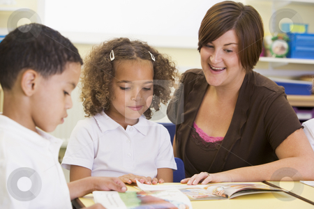 Schoolchildren and their teacher reading in a primary class stock photo,  by Monkey Business Images