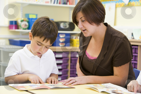 A schoolboy and his teacher reading in a primary class stock photo,  by Monkey Business Images