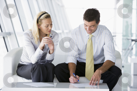 Two businesspeople sitting in office lobby talking and smiling stock photo,  by Monkey Business Images