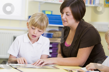 A schoolgirl and her teacher reading in a primary class stock photo,  by Monkey Business Images