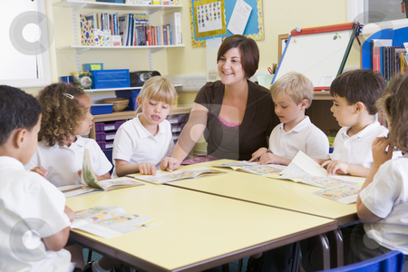 Schoolchildren and their teacher reading in primary class stock photo,  by Monkey Business Images