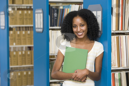 University student working in library stock photo, University student holding book in library by Monkey Business Images