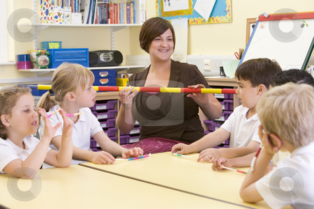 Schoolchildren and their teacher in a primary class stock photo,  by Monkey Business Images