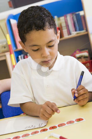 Boy learning to write numbers in primary class stock photo,  by Monkey Business Images