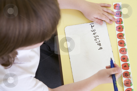 Girl learning to write numbers in primary class stock photo,  by Monkey Business Images