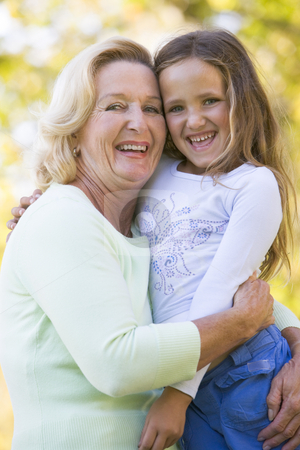 Grandmother and granddaughter outdoors and smiling stock photo,  by Monkey Business Images