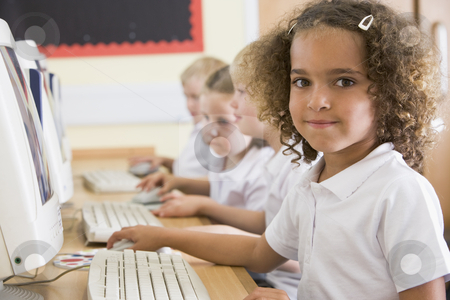 Girl working on a computer at primary school stock photo,  by Monkey Business Images