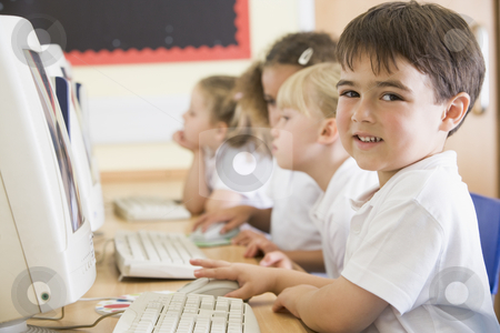 Boy working on a computer at primary school stock photo,  by Monkey Business Images