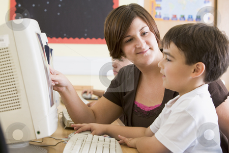 A boy and his teacher working on a computer at primary school stock photo,  by Monkey Business Images