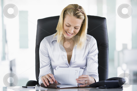 Businesswoman in office looking at personal organizer smiling stock photo,  by Monkey Business Images