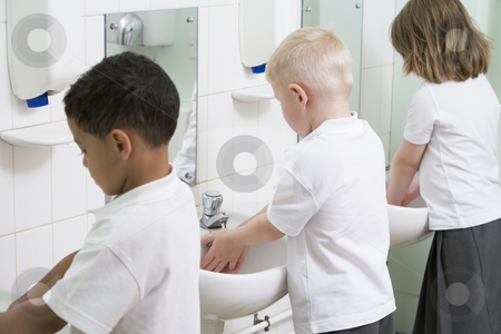 Children washing their hands in a primary school bathroom stock photo,  by Monkey Business Images