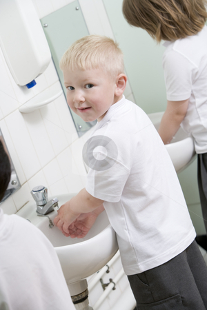 A boy washing his hands in a primary school bathroom stock photo,  by Monkey Business Images