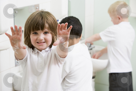 A girl displaying her hands in a primary school bathroom stock photo,  by Monkey Business Images
